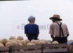 Amish man and woman with cantaloupes by Dennis L. Hughes